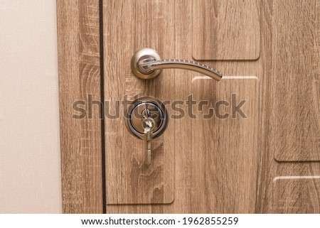 "Door handle and lock with keys close-up. Modern front door in color ""nut"". Royalty-Free Stock Photo #1962855259"