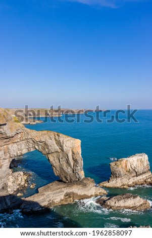 Beautiful natural archway and rugged ocean coastline (Green Bridge of Wales, Castlemartin, Pembroke) Royalty-Free Stock Photo #1962858097