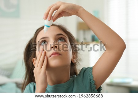 Adorable little girl using eye drops indoors Royalty-Free Stock Photo #1962858688