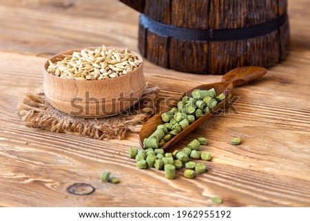 Barley in a wooden bowl, granulated hop in a spoon on a rustic table. Concept for craft beer and brewing Royalty-Free Stock Photo #1962955192