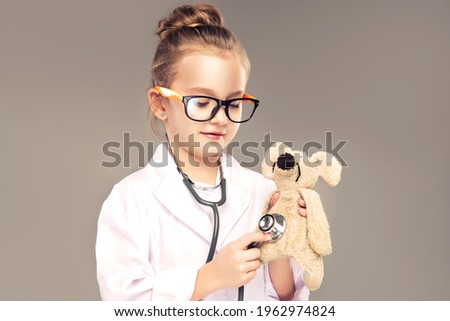 Child girl in a medical gown and stethoscope plays and pretends to be a doctor . Children choose a profession for the future. Happy and smiling baby in the game. Expressive facial emotions Royalty-Free Stock Photo #1962974824