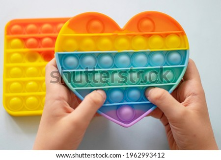 colorful antistress sensory toy fidget push pop it in kid's hands Royalty-Free Stock Photo #1962993412