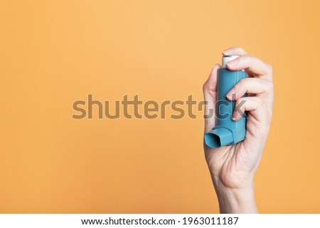 Hand holds inhaler to treat asthma. World Asthma Day. Concept of allergy care. Copy space Royalty-Free Stock Photo #1963011187