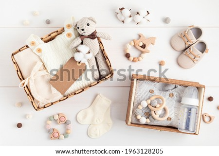 Gift basket with gender neutral baby garment and accessories. Care box of organic newborn cotton clothes Royalty-Free Stock Photo #1963128205