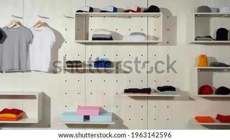 Assortment of colorful cotton sport clothes laid out on the shelves in the store. Custom wear at clothing printing company. Web Banner