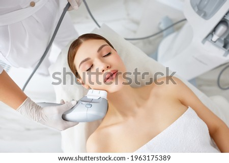 From above of relaxed young female client getting SMAS ultrasound face lifting massage with professional equipment in beauty center Royalty-Free Stock Photo #1963175389