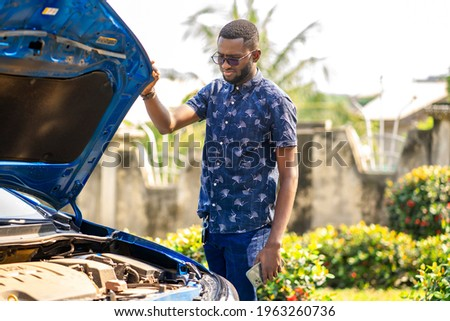 landscape view of african guy standing besides automobile, with opened bonnet- transportation concept Royalty-Free Stock Photo #1963260736
