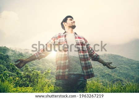 Double exposure of tourist caucasian man raise your hands to breathe pure air with mountain. Royalty-Free Stock Photo #1963267219