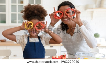 Happy excited mommy and daughter girl having fun while cooking in kitchen. Funny mom and kid making pepper slice glasses, cutting vegetables for salad. family eating at home. Head shot portrait