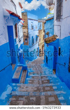 Narrow lane with steps in the blue medina of the Chefchaouen, Morocco. Blue city with traditional architecture in the Rif mountains of North Africa. Royalty-Free Stock Photo #1963273933