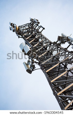 Mobile telephony base station. Metal mast structure with devices transmitting electromagnetic waves. 3G, LTE and 5g networks. Royalty-Free Stock Photo #1963304545