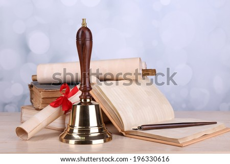 Gold school bell with school supplies on table on bright background #196330616