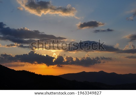 High resolution shot of sun behind clouds during sunset of hilly area of Himachal Pradesh, Beautiful view of colorful sunset - Stock Photo
