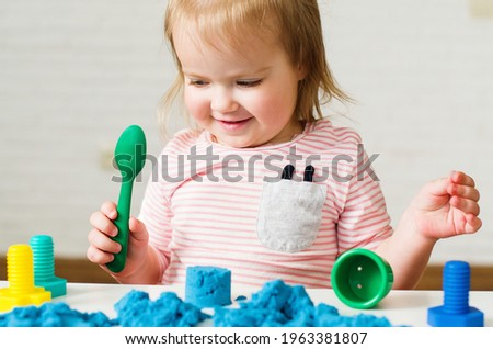 Little girl playing with blue kinetic sand. Educational games with children for fine motor skills. Sand therapy indoors. Concept of sensory and creativity game, therapy hand, development of fine motor Royalty-Free Stock Photo #1963381807