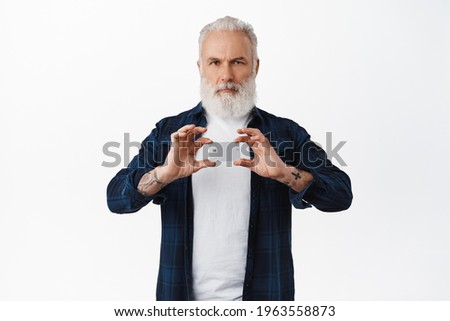 Serious senior man with long white beard and tattoos, shows credit card and frowns self-assured, stands against white background