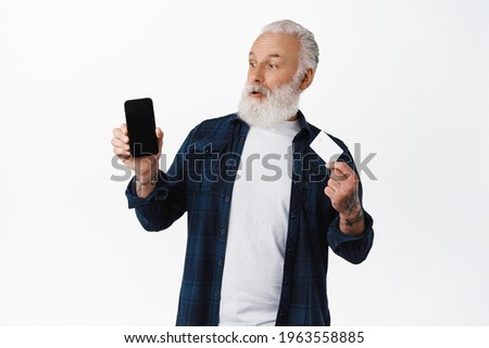 Surprised grandfather looking at smartphone screen as showing credit card, amazed by shopping online application, standing against white background