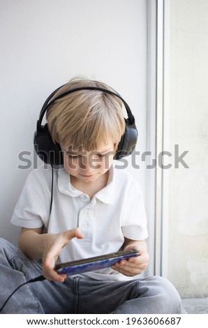 cute toddler boy in big headphones and a mobile phone, sits alone, plays games, watches cartoons or listens to music on a smartphone. Digital generation and telephone addiction concept