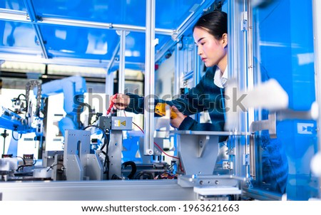 Asian Engineers Maintenance Robot Arm at Lab. they are in a High Tech Research Laboratory with Modern Equipment. Professional Japanese Development Engineer Testing an Artificial Intelligent. Royalty-Free Stock Photo #1963621663