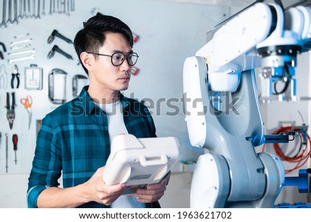 Asian Engineers Maintenance Robot Arm at Lab. they are in a High Tech Research Laboratory with Modern Equipment. Professional Japanese Development Engineer Testing an Artificial Intelligent. Royalty-Free Stock Photo #1963621702