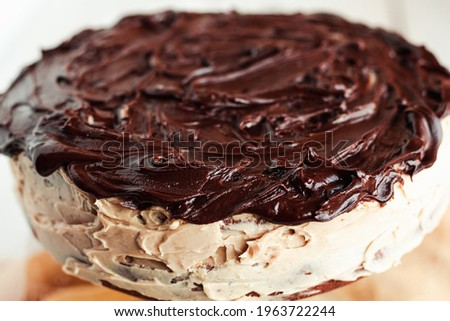 Delicious round cake with white buttercream topped with chocolate frosting, coating.Holiday and festive food concept. Royalty-Free Stock Photo #1963722244