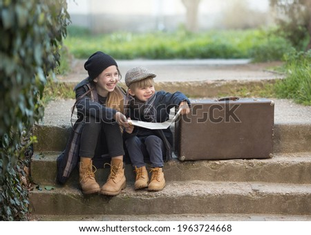 Children a boy and a girl sit with a suitcase and a map on the steps and laugh merrily. They're on a journey. they are wearing fashionable vintage clothes Royalty-Free Stock Photo #1963724668