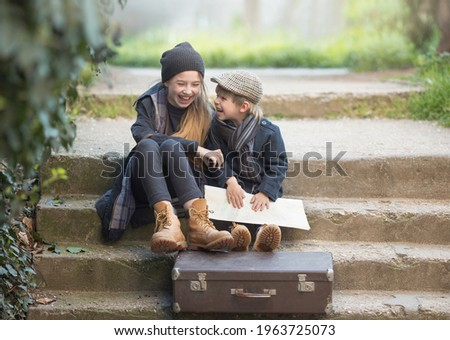 Children a boy and a girl sit with a suitcase and a map on the steps and laugh merrily. They're on a journey. they are wearing fashionable vintage clothes Royalty-Free Stock Photo #1963725073