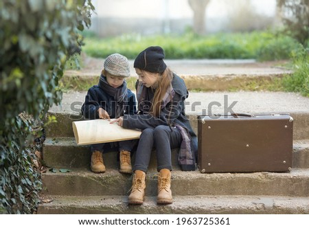 Children a boy and a girl sit with a suitcase and look at the road on the map. They're on a journey. they are wearing fashionable vintage clothes. Royalty-Free Stock Photo #1963725361