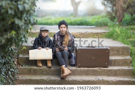 Children a boy and a girl sit sad because they are lost. They're on a journey. they are wearing fashionable vintage clothes, в руках карта и чемодан Royalty-Free Stock Photo #1963726093