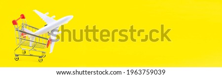 Flight sale concept. Vacation travel tour. Tourism opening. Plane in a shopping cart on trendy yellow background panorama banner. Cheap flights.
