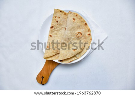 Indian vegan diet meal- fresh organic whole wheat chapathi or chapati served with delicious vegetable curry and chickpeas channa masala. with wood plate and whit