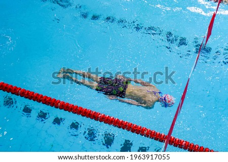 swimmer in the blue water of the pool, photo from top to bottom, swims under water in black swimming trunks, rubber cap, sports lifestyle