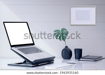 Mockup blank screen laptop computer on wooden stand with keyboard and mouse on white top table. Royalty-Free Stock Photo #1963935160
