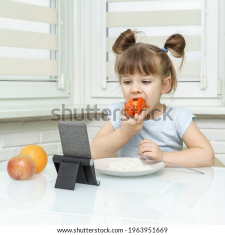 child girl eating food and watching cartoons on a smartphone