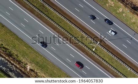 Aerial top down picture three lane major highway traffic driving in both ways showing vehicles on all lanes stabilized camera moving over the roads in evenly way Royalty-Free Stock Photo #1964057830