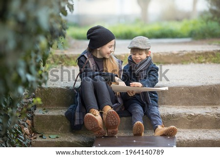 Children a boy and a girl sit with a suitcase and a map on the steps and laugh merrily. They're on a journey. they are wearing fashionable vintage clothes Royalty-Free Stock Photo #1964140789