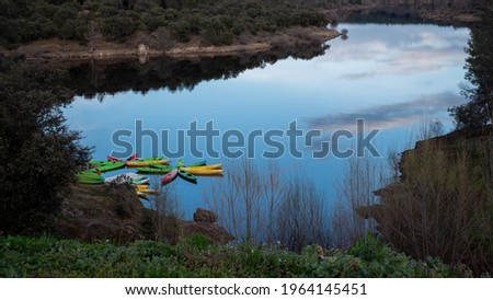 A wide picture of a lake with some kayaks moored  The sky is reflected in the water