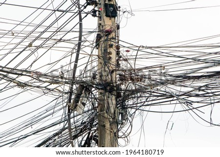 messy electricity wires on the pole, The chaos of cables and wires on an electric pole in Thailand Royalty-Free Stock Photo #1964180719