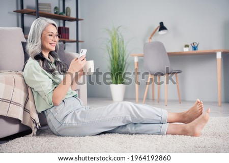 Full size profile portrait of positive pretty lady sit on carpet hold tea mug look phone typing blogging indoors