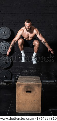 Young active strong fit sweaty muscular man with big muscles doing box jump workout in the gym as hardcore cross training real people exercise Royalty-Free Stock Photo #1964337910