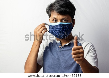 An Indian man shows thumbs up to double masking during covid-19 pandemic, healthcare concept Royalty-Free Stock Photo #1964437153