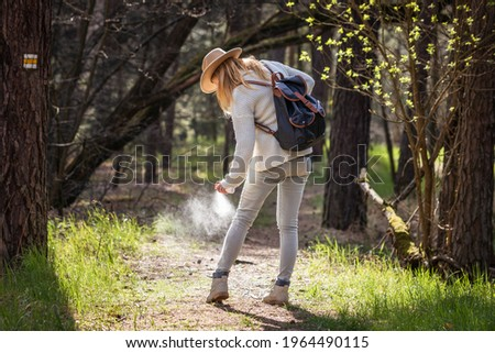 Woman spraying insect repellent against tick at her legs. Protection against mosquito bite during hike in woodland Royalty-Free Stock Photo #1964490115