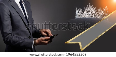 Business people follows News of Miss Beauty Queen Pageant Contest on digital social media in smart phone. Background of Sash and Diamond Crown Royalty-Free Stock Photo #1964552209