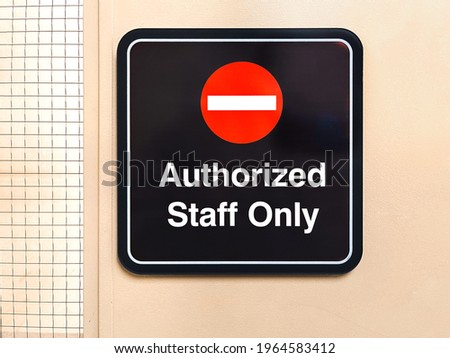Close up of Authorized Staff Only sign on light yellow metal door with mesh wire pattern side window.