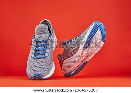Stability and cushion running shoes. New unbranded running sneaker or trainer on orange background. Men's sport footwear. Pair of sport shoes. Royalty-Free Stock Photo #1964675209