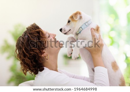 Woman playing with dog. Young woman with curly hair hugging puppy indoors. Family with pet at home. Fun with domestic animal. Love and friendship with pets. Royalty-Free Stock Photo #1964684998