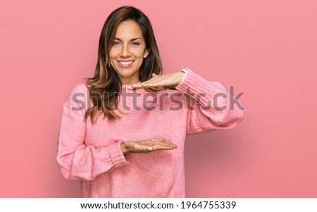Young hispanic woman wearing casual clothes gesturing with hands showing big and large size sign, measure symbol. smiling looking at the camera. measuring concept.