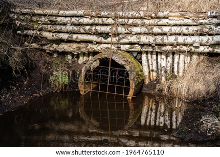 a small water channel in a swamp with a culvert above which the fortification is made of birch trunks