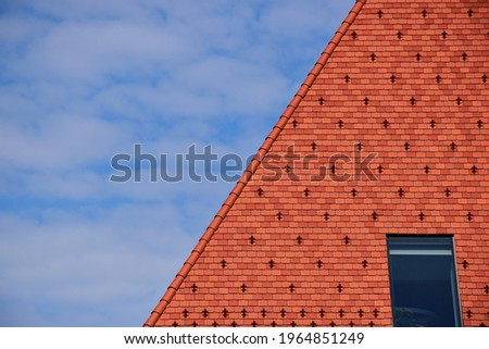 clay tile roof. steep slope in red brown color. bright blue sky wand white clouds. roof window or skylight. metal ice and snow guard in square pattern. modern new construction concept. snow breaker Royalty-Free Stock Photo #1964851249