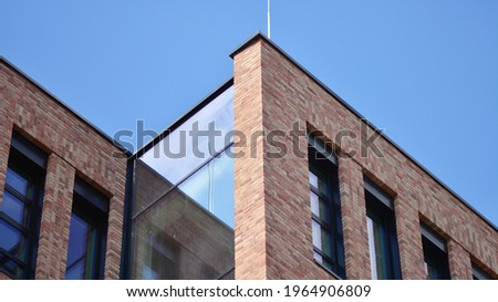 Modern brick and glass facade of the office building.  A contrasting combination of sky and brick texture on a building. Architectural facade of a red brick building.. Royalty-Free Stock Photo #1964906809