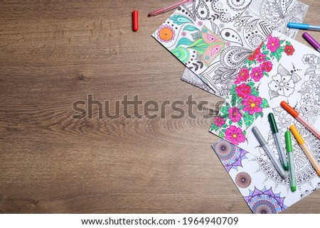 Antistress coloring pages and felt tip pens on wooden table, flat lay. Space for text Royalty-Free Stock Photo #1964940709